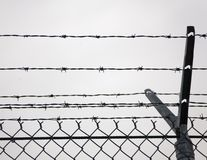 Security Fence. Post of a chain-link fence topped with barbed wire Royalty Free Stock Photos
