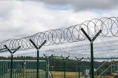 Security fence with a barbed wire. Stock Photo