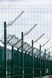 Security fence in prison. Wired fence with rolled barbed wires on white background Royalty Free Stock Images