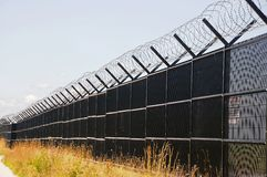 Security fence topped with barbed wire. Royalty Free Stock Photography