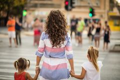 Security first of all. Mother walking with her daughter walking over the pedestrian crossing. From back. Close up. Copy space royalty free stock image