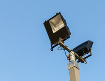 Security floodlights on a tall post against a winter blue sky at. A UK shopping centre Royalty Free Stock Image