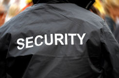Security guard. Back of a security guard in front of blurred crowd Stock Photos