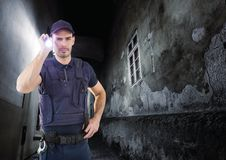 Security guard in a alley at night with torch. Digital composite of security guard in a alley at night with torch Stock Photo
