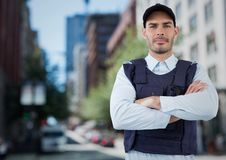 Security guard with arms folded against blurry street. Digital composite of Security guard with arms folded against blurry street Stock Image