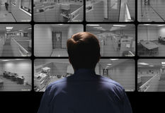 Security guard conducting surveillance by watching several secur Royalty Free Stock Images