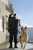 Security Guard With Dog On Patrol. Full length of a security guard with trained dog on patrol Royalty Free Stock Image