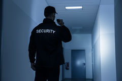Security Guard With Flashlight In Building Corridor. Rear view of security guard with flashlight in building corridor Stock Photo