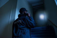 Security Guard With Flashlight. Rear View Of Male Security Guard Holding Flashlight Royalty Free Stock Images