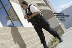 Security Guard With Gun Patrolling. Low angle view of security guard with gun patrolling outside house Stock Images