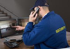 Security guard in his office phoning and pointing something in the screen. Digital composite of security guard in his office phoning and pointing something in Stock Image