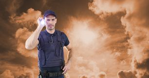 Security guard holding flashlight against sky during sunset. Digital composite of Security guard holding flashlight against sky during sunset Royalty Free Stock Photo