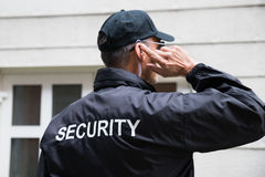 Security Guard Listening To Earpiece Against Building Stock Photography