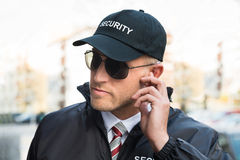 Security Guard Listening To Earpiece. Portrait Of Young Male Security Guard Listening To Earpiece royalty free stock photo