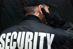 Free Security Guard Listens To Earpiece, Back Of Jacket Showing Royalty Free Stock Image - 37761446