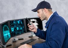 Security guard with locks on the screens speaking with the walkie-talkie in his office. Digital composite of security guard with locks on the screens speaking stock photo