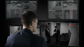 Security guard looking in corporative surveillance cameras, crime scene witness. Stock footage stock footage