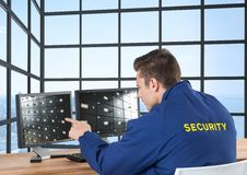 security guard looking the image of the security camera ion the screens in his office stock photo
