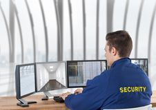 Security guard looking the images of the security cameras on the screens, in the office. Digital composite of security guard looking the images of the security stock photo