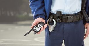 Security guard lower body with walkie talkie against blurry street. Digital composite of Security guard lower body with walkie talkie against blurry street stock photos