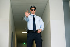 Security Guard Making Stop Gesture. Young Male Security Guard Making Stop Gesture At The Entrance Royalty Free Stock Photos