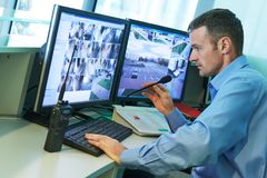 Security worker during monitoring. Video surveillance system. Security guard man monitoring objects. Video surveillance system stock image