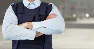 Security guard mid section arms folded against blurry street. Digital composite of Security guard mid section arms folded against blurry street Royalty Free Stock Photos