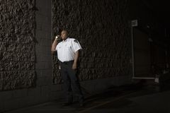 Security Guard Patrols At Night With Torch. Young male security guard in uniform patrols at night with torch royalty free stock image