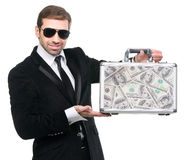 Security guard presenting a metal suitcase full of US dollars Royalty Free Stock Images