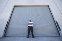 Security Guard Protects Warehouse Entrance. Low angle view of a young security guard standing with arms crossed in front of warehouse entrance Royalty Free Stock Photos