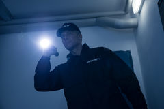 Security Guard Searching With Flashlight In Office. Mature security guard searching with flashlight in office building Royalty Free Stock Photo