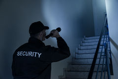 Security Guard Searching On Stairway With Flashlight. Rear view of security guard searching on stairway with flashlight in office building stock photography