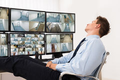 Security Guard Sleeping In Control Room. Security Guard Sleeping In Front Of Multiple Computers Showing CCTV Footage stock images