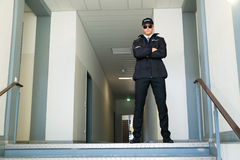 Security Guard Standing At The Entrance. Male Security Guard Standing With Folded Arms At The Entrance Stock Photo
