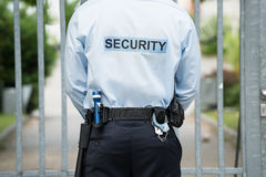 Security Guard Standing In Front Of Gate. Rear View Of A Security Guard Standing In Front Of Gate Stock Photo