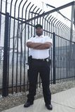 Security Guard Standing In Front Of Prison Fence. Confident security guard standing with arms crossed in front of the prison fence stock photography