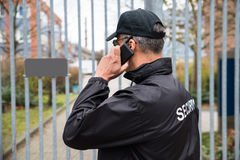 Security Guard Talking On Mobile Phone In Front Of Gate. Confident mature security guard talking on mobile phone in front of gate royalty free stock photos