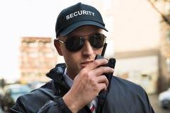 Security Guard Talking On Walkie-talkie Royalty Free Stock Photo