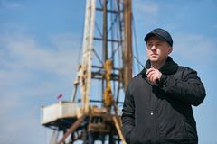 Security guard using portable wireless transceiver. Security man with walkie talkie, standing outdors against oil drilling station platform, safety concept Royalty Free Stock Photography