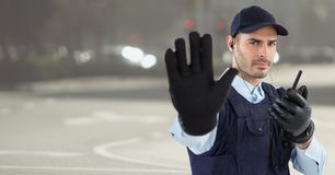 Security guard with walkie talkie and hand up against blurry street. Digital composite of Security guard with walkie talkie and hand up against blurry street royalty free stock photos