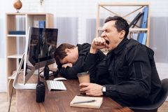 The security guard who sits in front of the monitor yawns. Near his colleague. They are in the security room Stock Photos