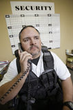 Security Guard At Work. Caucasian security guard using telephone in office royalty free stock photos