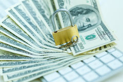 Security lock on dollar bills with white computer keyboard Stock Photos