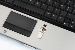 Security lock on laptop computer keyboard. Next to the touch pad. The lock is used to unlock the computer and gain access to all files Stock Photography