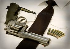 Security magnum revolver. Magnum revolver and seven bullets laying on a white security shirt Stock Photo