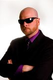 Security Man. A bald, serious, security man wearing sunglasses with an earpiece and a suit Stock Photo
