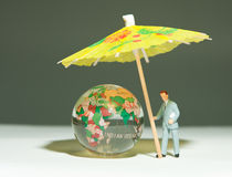 Security man holding umbrella under globe Stock Photo