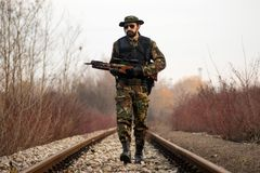 Security man with crossbow. The security man in military uniform with crossbow weapon is walking on the railway track in nature Royalty Free Stock Photography