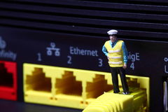 Security man router A. Miniature model security man standing on broadband router connector Stock Photo