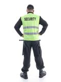 Security guard. Security man wearing black uniform and yellow reflective vest standing confidently with arms resting on hips, facing back, shot on white royalty free stock photography
